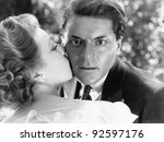 Close-up of a young man being kissed by a young woman and looking surprised - stock photo