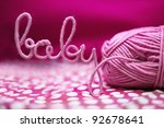 baby word made of yarn among pink textile - stock photo