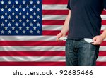 poor man showing empty pockets in front of us flag - stock photo