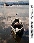Small boat on bay still water - stock photo