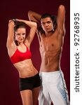 strong young man and woman with dumbbells - stock photo