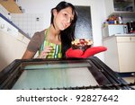 woman fetching a cake from an oven - stock photo