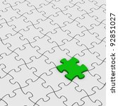 gray jigsaw puzzles with one green piece - stock photo