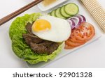 Cambodian (Loc Lac) / Vietnamese (Bo Luc Lac) stir-fried beef salad - Shaking Beef. Topped with fried egg and served with a lime and black pepper dip. - stock photo
