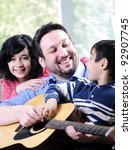 Happy family playing guitar together - stock photo