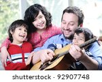 Happy family playing guitar together at home - stock photo
