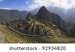 Machu Picchu, main gate, surrounding wall and exterior stairway under uneven sunlight. Wayna Picchu and surrounding mountains in the background. - stock photo