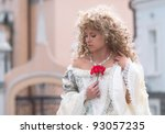 Beautiful young woman in medieval  dress with the red flower - stock photo