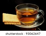 Cup of tea and biscuits on black background - stock photo