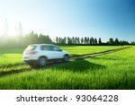 Stock photo spring field and blurred car on ground road 93064228