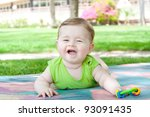 Smiling baby lying and played in the park - stock photo