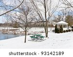 Winter city scene with a picnic table and gazebo at neighborhood recreation area. - stock photo