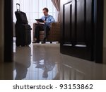 Stock photo mid adult caucasian manager typing on tablet pc in hotel room during business travel low angle 93153862