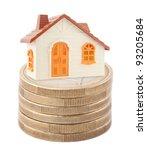 Orange toy house on stack of euro coins - stock photo