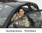 The girl in a fur coat sitting in the car - stock photo