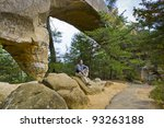 Hiking man sitting on a rock under natural stone bridge, resting and enjoying the view. - stock photo