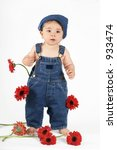 Small photo of Flower Girl - Standing nine mth old baby girl wearing a bib n brace denim overalls. Red gerbera daisies scattered about