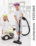 Tidy up day - children cleaning their room using the vacuum cleaner - stock photo