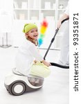 Little girl helping mother to clean the room - sitting on the vacuum cleaner - stock photo