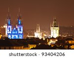View of prague rooftops with the blue illuminated spires of Tyn church in Old Town Prague, Czech Republich
