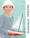 Summer holiday - little sailor dreaming about sailing - stock photo