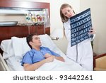 Doctor and patient examining X-ray report in hospital - stock photo