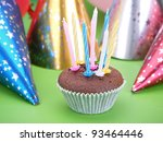 Chocolate muffin decorated with eight candles with party cone caps in the background - stock photo