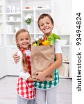 Happy healthy kids in the kitchen with the grocery bag full of vegetables - stock photo