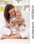 Look what a cute little ... woman and little girl watching a baby booklet - stock photo