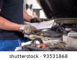 Detail of a mechanic holding a service order with a dirty glove on - stock photo