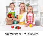Woman and kids unpacking the groceries in the kitchen - stock photo
