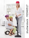 Happy family cleaning their room using the vacuum cleaner - stock photo