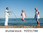 Summer vacation - family playing with skipping rope on the beach - stock photo