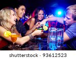 Stock photo image of happy girl looking at her glass while young man pouring cocktail into it with friends near 93612523