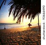 Surfers Walk Along Beach At...