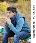 Young stylish man portrait sitting in autumn park. Outdoor. - stock photo