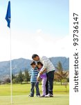 Father teaching his kids how to playing golf - stock photo