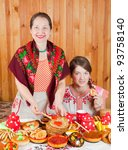 Happy mother with teenager daughter eating pancake with caviare during  Shrovetide - stock photo