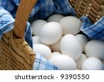 Fresh eggs in a woven basket with blue and white dish towel. Selective focus on eggs with shallow dof.  Concept - all eggs in one basket. - stock photo