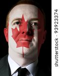 High key portrait of a serious businessman or politician whose face is painted in national colors of canada flag - stock photo