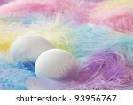 Easter background image of eggs nestled on a bed of soft pastel colored feathers.  Macro with extremely shallow dof.  Selective focus on closest egg. - stock photo