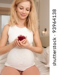 Young pregnant blonde with present in bedroom in the morning - stock photo