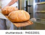 Male Baker Baking Fresh Bread...