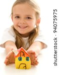 Happy little girl with hand made clay house - new home concept, isolated - stock photo