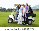 Beautiful family portrait with a golf cart at the course - stock photo