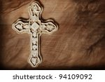 Artistic macro image of ornate stone cross on wood background with layers of texture added for effect.  Copy space included in design. - stock photo