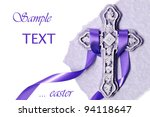 Easter background image of small ornate stone cross with purple satin ribbon and parchment paper on white background with copy space. - stock photo