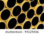 Background of stack of yellow and black plastic pipes - stock photo