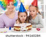 Birthday girl making a wish and blowing out candles on a cake - stock photo