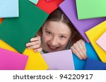 Happy young girl emerging from beneath books - education and learning concept - stock photo